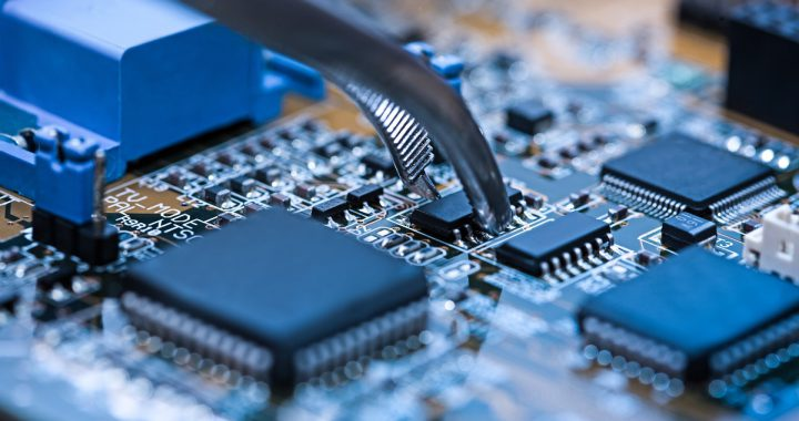 Close,Up,On,Tweezers,Holding,Chip,On,Computer,Circuit,Board.